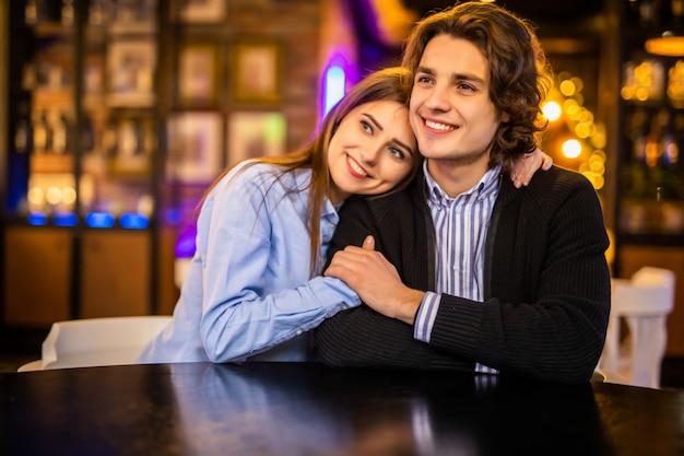 カフェを抱いて幸せな若い夫婦。