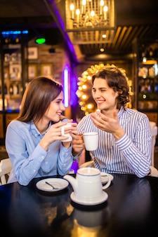 幸せな若い男と女のカフェでお茶を飲む