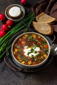 伝統的な料理のロシア料理。暗い石造りのカウンタートップのボウルにクワス、ソーセージ、野菜を入れた冷たい夏のオクローシカスープ。コピースペース。