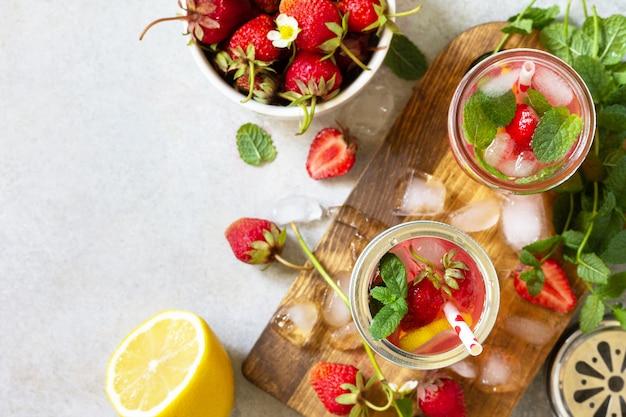 さわやかな夏の飲み物。新鮮なイチゴ、氷、レモンとレモネード、明るい石のカウンターコピースペース。