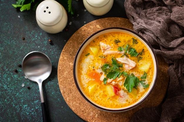 Норвежский суп с кремом и лососем на деревенском деревянном столе на фоне темного камня