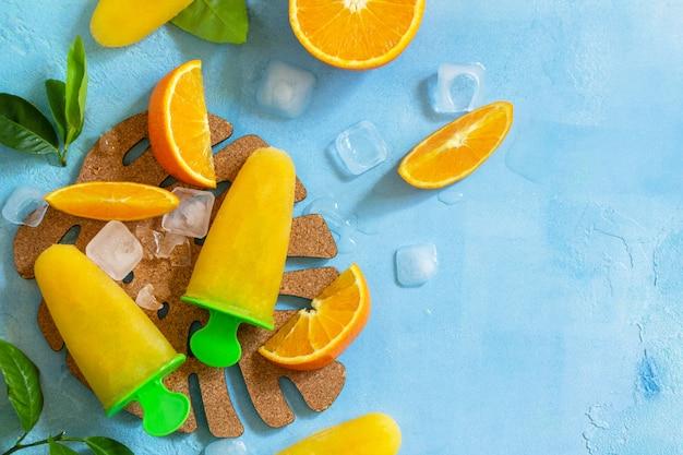 オレンジジュース、フルーツアイス、青い石やスレートの背景にロリポップと自家製アイスキャンデースペースをコピーします。