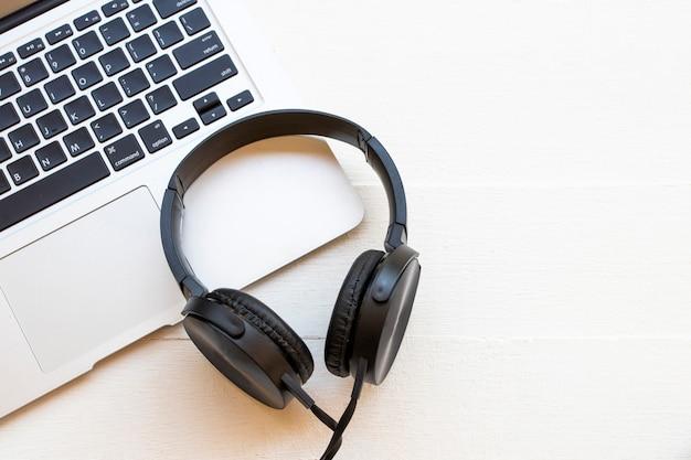 ライフスタイルのリスニングの黒いヘッドフォンとコンピューターのノートブック