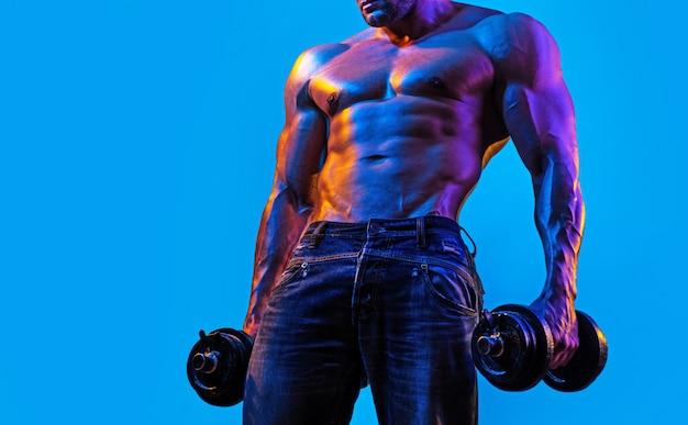 青の背景にダンベルでワークアウトの強い男