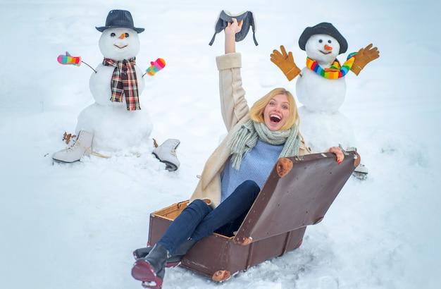 雪だるまの背景にスーツケースを持つ女性