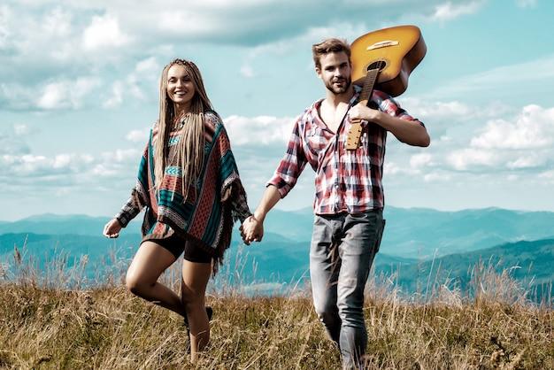 美しい山の背景に人生を楽しんでいるカップル。幸せな恋人たちは手をつないでいます。