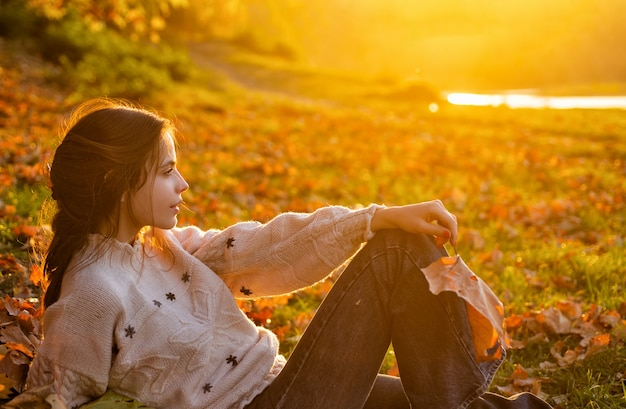 秋の夕方の日没で美しいブルネットの女性。川のベンチで落ち葉で若い女の子の残り。秋の人々の概念。
