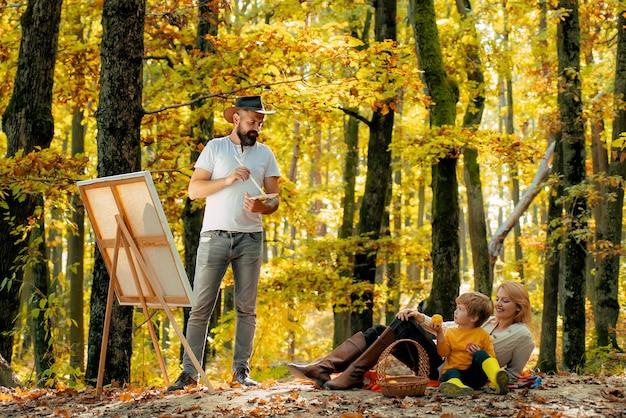 秋の休暇で幸せな家族。彼女の妻と息子を探している父の画家。概念。