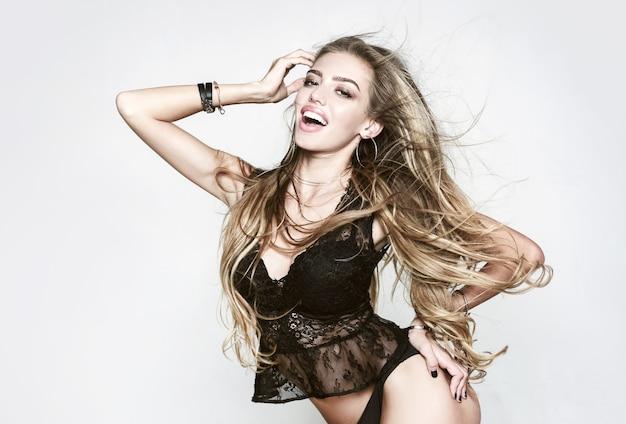 セクシーな興奮している女の子。長い髪と完璧な肌が灰色の背景でポーズ美しい若いブロンドの女性。