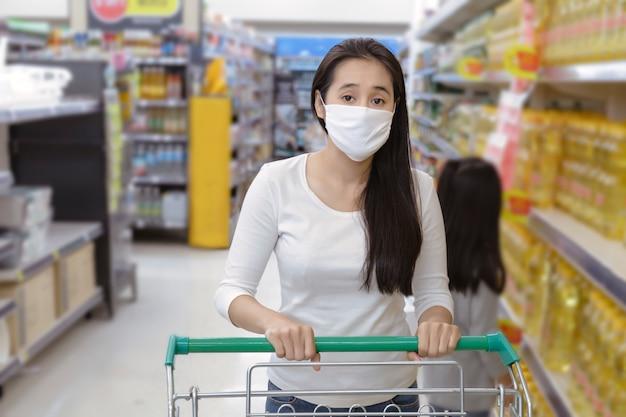 アジアの女性は、スーパーマーケットのデパートでフェイスマスクプッシュショッピングカートを着用します。