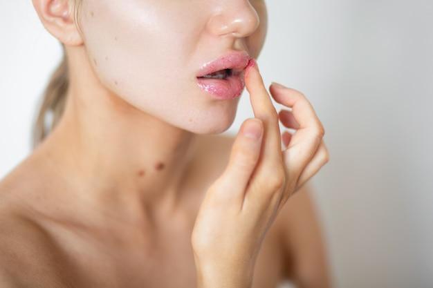 Красивая женщина наносит скраб на губы