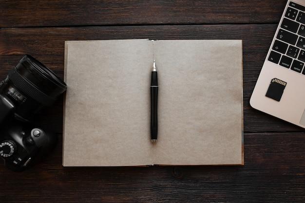 Ноутбук, флэш-накопитель, блокнот, ручка и фотоаппарат на темном деревянном столе