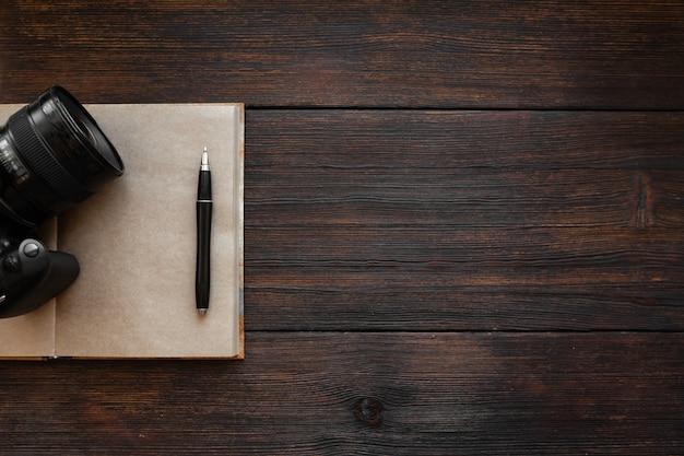Блокнот, ручка и фотоаппарат на темном деревянном столе