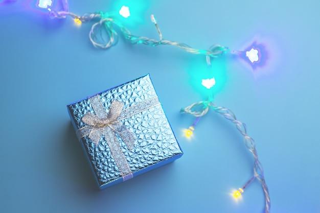 クリスマスツリーのライトと青いギフトボックス