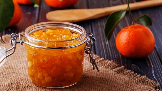 Апельсиновое (мандариновое) варенье в стеклянной банке на столе.