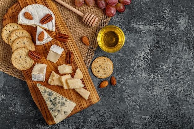 Ассорти из сыров с медовыми орехами и виноградом на разделочной доске