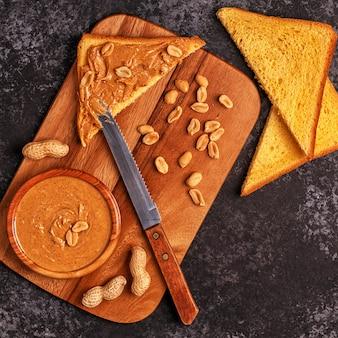 木の板にパンのスライスとピーナッツバターのボウル