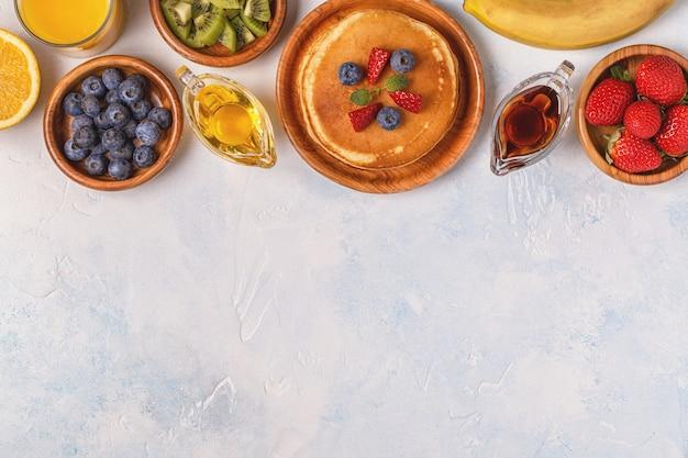 フルーツ、蜂蜜、メープルシロップのパンケーキ