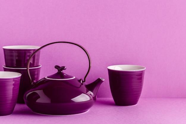 紫のティーポットと薄紫色の背景の上にカップ