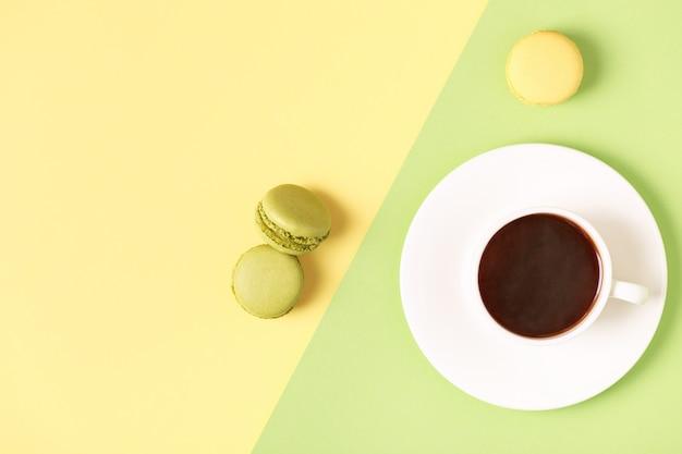 パステル背景にマカロンとコーヒーのカップ