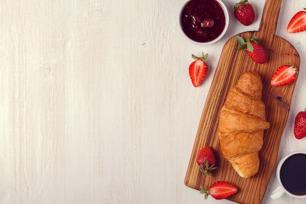 クロワッサン、ジャム、フルーツ、コーヒーを含む朝食。