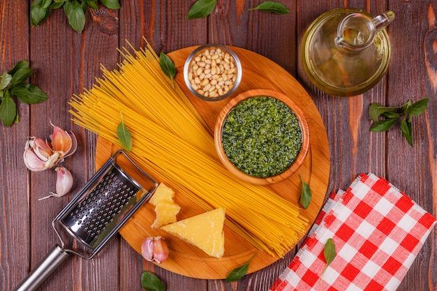 Зеленый песто базилика - итальянский рецепт ингредиенты на деревянный стол.