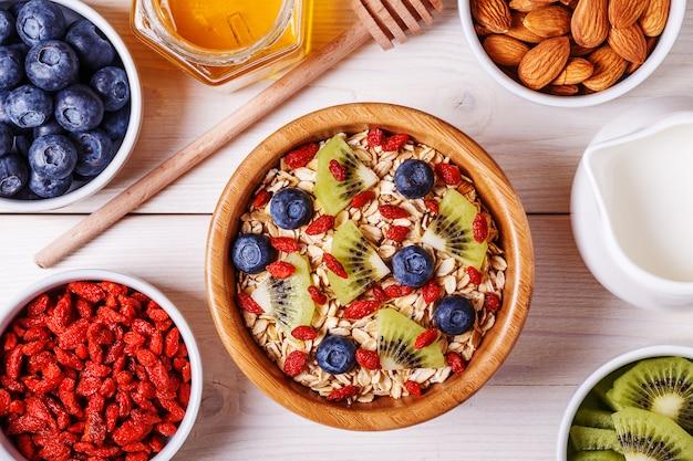 Здоровый завтрак - миска овсяных хлопьев со свежими фруктами, миндалем и медом.