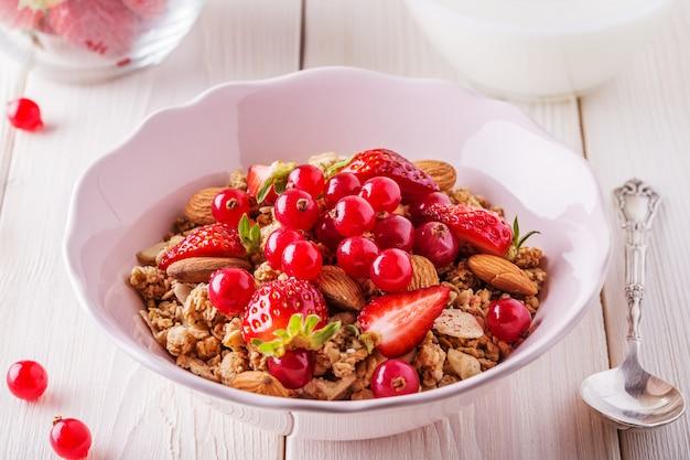 Здоровый завтрак - миска овсяного мюсли со свежими фруктами, миндалем и белым шоколадом.