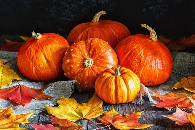 木製のカエデの葉と秋のカボチャ。