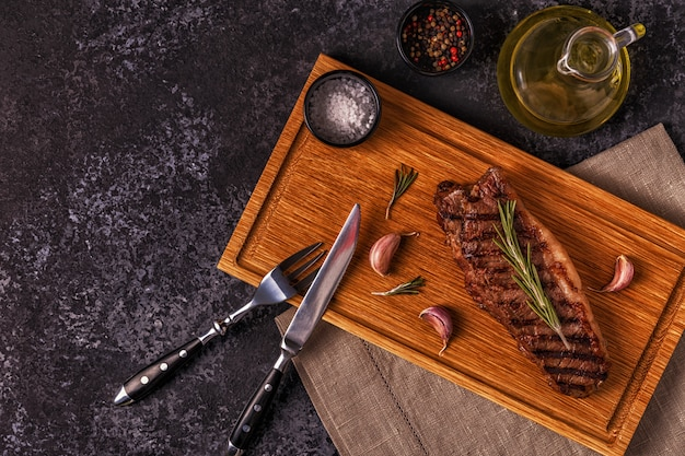 暗いテーブルで牛肉ステーキ。