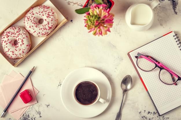 メモ帳、ドーナツ、白いテーブルの上のコーヒー。