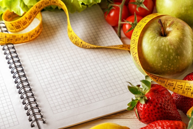 Свежие органические овощи и фрукты, открытый блокнот и ручка