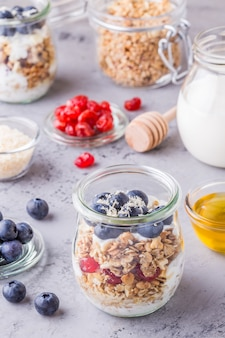 ヘルシーな朝食-コーンフレークのガラス瓶に新鮮なフルーツ、ヨーグルト、蜂蜜。