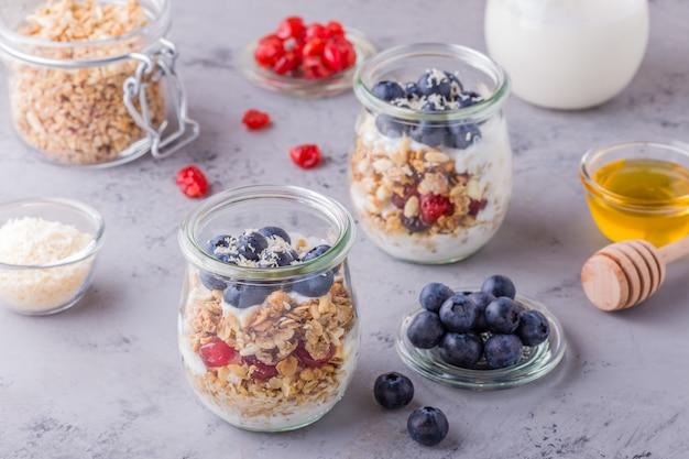 Здоровый завтрак - стеклянные банки из овсяных хлопьев со свежими фруктами, йогуртом и медом.