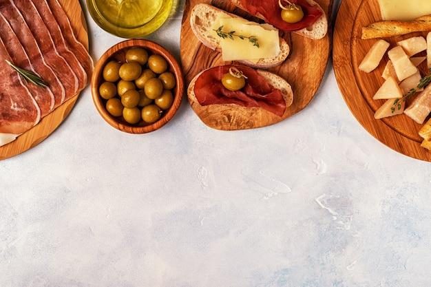 Итальянская еда стол с ветчиной, сыром, оливками.