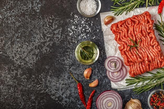 玉ねぎ、ハーブ、調味料を添えた紙に刻んだ生肉