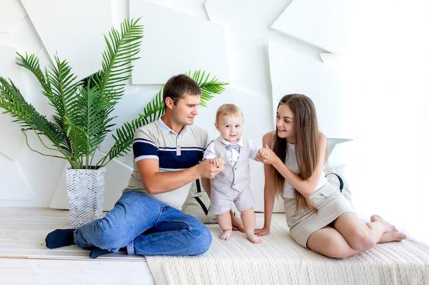 Молодая мама и папа с ребенком на руках, родители с ребенком, день семьи
