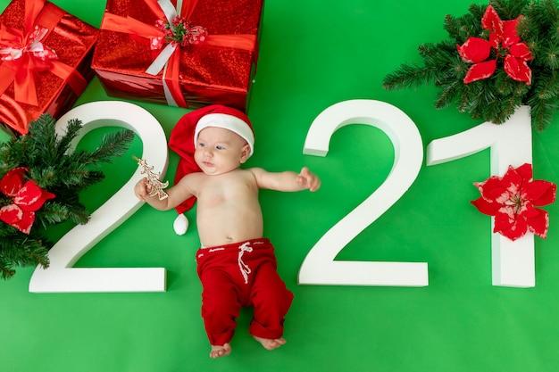 緑の背景の上に横たわるサンタ衣装の赤ちゃん
