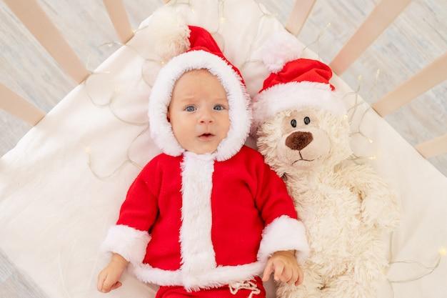 自宅のベビーベッドで横になっているサンタ衣装の赤ちゃんのクリスマス写真
