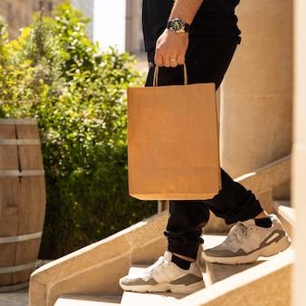 買い物袋で階段を下りて行く男