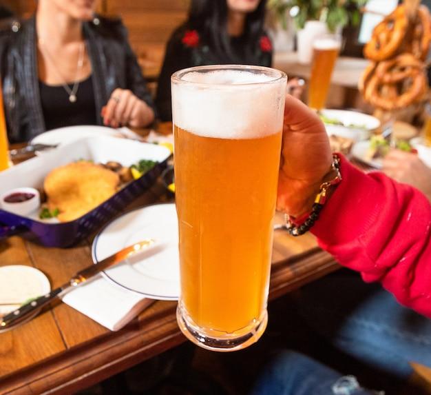 ビールジョッキ、友人、レストランを持って男