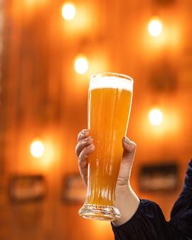 背景のボケ味を持つレストランでガラス、ビールジョッキを保持している女性