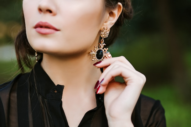 ブルネットの少女のポートレート、クローズアップ。若い女性が宝石でイヤリングに触れます。内側に黒い石が入ったゴールドのイヤリング。高価なジュエリー。