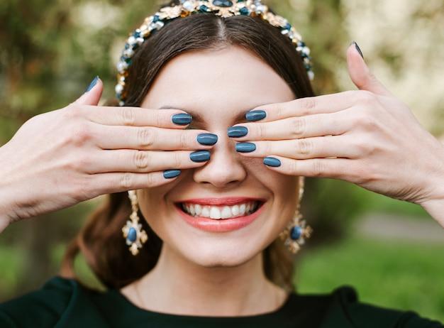 明るいマニキュアを持つ若い幸せな女は、広い白い笑顔、まっすぐな白い歯を笑顔します。女の子は手で顔を覆っています。
