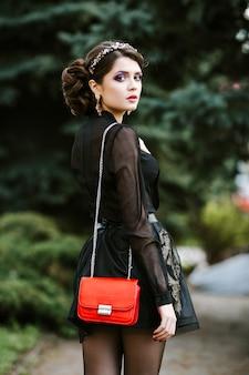 若いスタイリッシュな女性のライフスタイルの肖像画は、赤いトレンディなバッグが付いている都市に行きます。