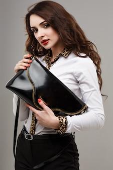 トレンディな黒の財布を持つ美しい少女。ファッショナブルな黒の財布、白いシャツ、黒のズボン、アクセサリーのイヤリングで、合計の黒と白の服を持つスタイリッシュな女性のイメージ。赤い唇。