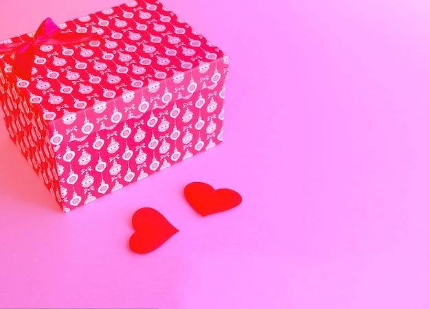 ピンクのトレンディな表面に赤いリボンで結ばれた赤いギフトボックス