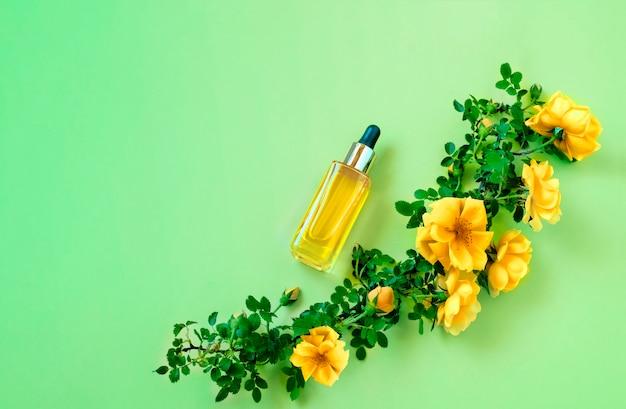 Эфирное масло в стеклянной прозрачной бутылке и цветы