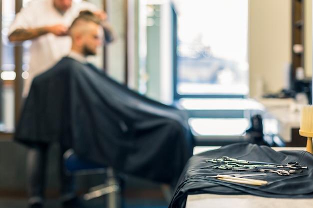 Роскошный интерьер парикмахерской, дорогая синяя мебель, деревянная отделка, модный черный потолок, белые одежды на спинках кресел
