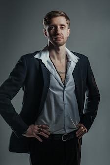 スーツを着た若くてかっこいい男とスタジオで灰色のポーズをとる多くのゴールデンリング。